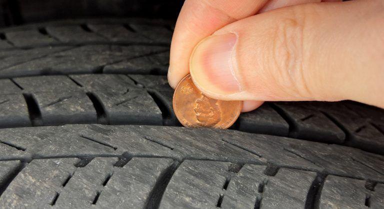 prsona pasando una moneda por las ranuras de un neumático
